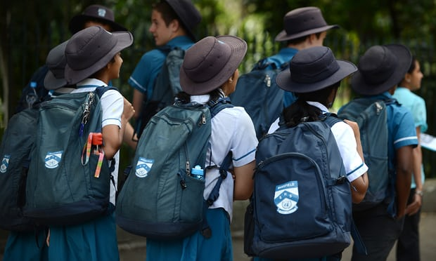 Photo of primary school students with backpacks and hats